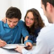 Young attractive couple signing contract — Stock Photo
