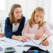 Woman helping out her little sister for homework — Stock Photo #54483091