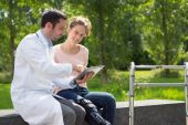 Doctor showing reeducation's tips on tablet — Stock Photo