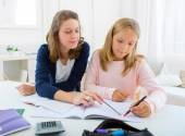 Woman helping out her little sister for homework — Stock Photo