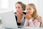 Attractive woman and little sister videocalling — Stock Photo