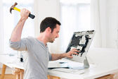 Young attractive man angry against computer — Stock Photo