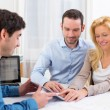 Young attractive couple signing contract on tablet — Stock Photo #58141459