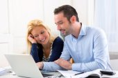 Young attractive couple using laptop at home — Photo