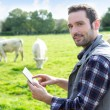 Young attractive farmer using tablet in a field — Stock Photo #58644531