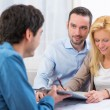 Young attractive couple signing contract — Stock Photo #58644593