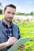 Young attractive farmer working in a field — Stock Photo
