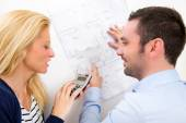 Young couple studying plans of their future house — Stock Photo