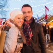 Young attractive couple in a christmas market — Stock Photo #58707991