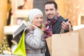 Young attractive couple with shopping bags — Stock Photo