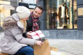 Young attractive couple putting gift in bags — Stock Photo