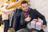 Young attrative man preparing gift surprise — Stock Photo
