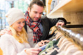 Young man helping his wife to choose clothes — Stock Photo