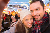 Young attractive couple in a christmas market — Stock Photo