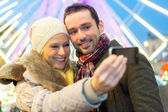 Young attractive couple in a christmas market — Photo