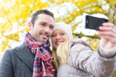 Young attractive couple taking selfie in a parc — Stock Photo