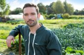 Young attratcive farmer in front of garden — Stock Photo