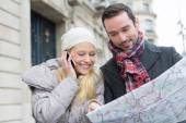 Couple of young attractive tourist watching map — Stock Photo