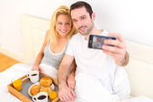 Young attractive couple taking selfie during breakfast  — Stock Photo