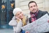 Couple of young attractive tourist watching map  — Zdjęcie stockowe