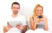 Young attractive couple using mobile and tablet in bed — Stock Photo