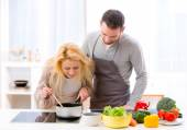 Young attractive woman give food to her husband to taste — Stock Photo