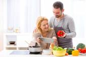 Young attractive couple reading recipe on a  tablet — Stock Photo