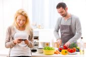 Young attractive woman writing text in kitchen — Stock Photo