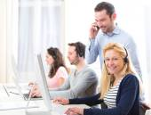Manager training a young attractive people on computer — Stockfoto