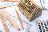 House miniature under construction on an architect desk — Stock Photo