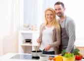 Young attractive couple cooking in a kitchen — Stock Photo