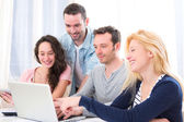 Group of 4 young attractive people working on a laptop — Stock Photo