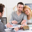 Young attractive couple signing contract with real estate agent — Stock Photo #66262083