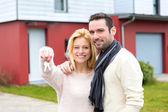 Young happy couple in front of their new house — Stock Photo
