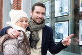 Young attractive couple in front of an agency — Stock Photo