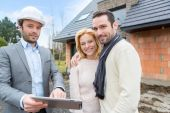 Real estate agent and a young couple in front of future home — Stock Photo