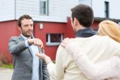 Real estate agent delivers keys to young atractive couple — Stock Photo
