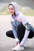 Young attractive woman tying shoelaces before a running session — Stock Photo
