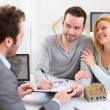 Young attractive couple signing contract with real estate agent — Stock Photo #68098969
