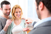 Real estate agent delivers keys of new house to young couple — Stock Photo