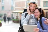 Couple of attractive tourists using tablet and smartphone  — Stock Photo