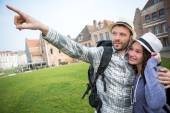 Couple of young attractive tourists discovering city — Stock Photo