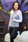 Young attractive woman adjust her music player before running — Stock Photo