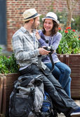 Young couple of tourist watching photographs during a break — Stock Photo