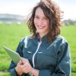 Young attractive farmer in a field using tablet — Stock Photo #70759121