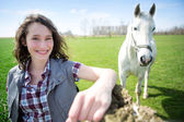 Portrait of a young attractive farmer in fields with horse — Stock Photo
