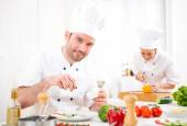Young attractive professional chef cooking in his kitchen — Stock Photo