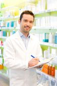 Attractive pharmacist taking notes at work — Stock Photo