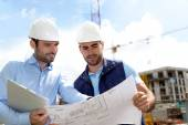 Engineer and worker checking plan on construction site — Stock Photo