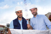 Engineer and worker watching blueprint on construction site — Stock Photo